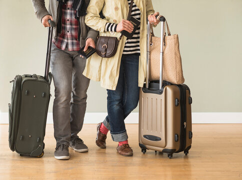 Couple holding rolling luggage in living room