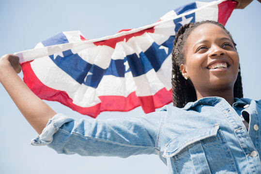 Black woman carrying American flag banner