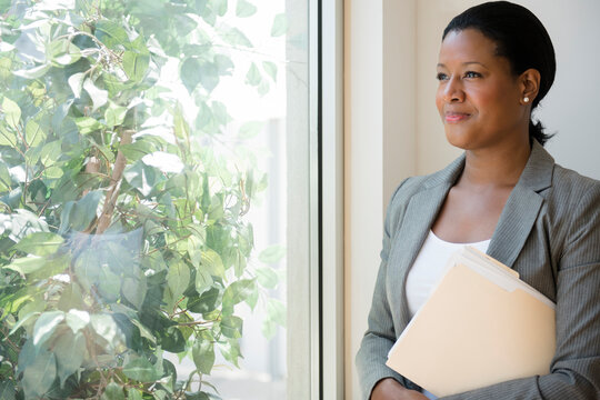 Black businesswoman looking out window
