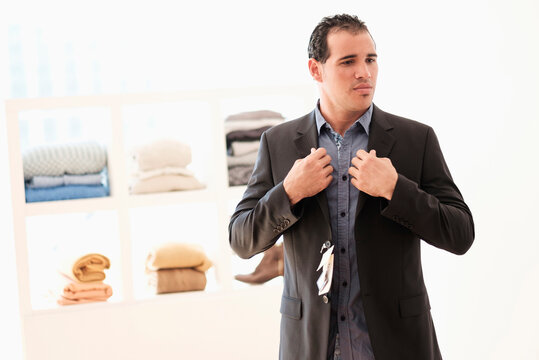 Hispanic man trying on suit in store