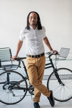 Black businessman with bicycle in office