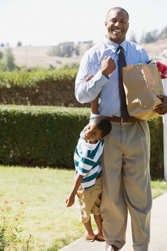African father carrying groceries and son