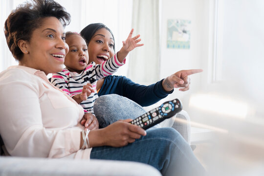 Black multi-generation family watching exciting television