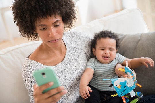Mother holding crying baby son while texting on cell phone