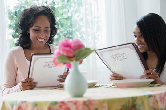 Mother and daughter reading menus in restaurant
