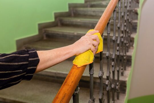 A cleaner hand with black sleeve holding yellow micro fiber cloth wiping the wooden top of railing in interior with staircase and green wall.