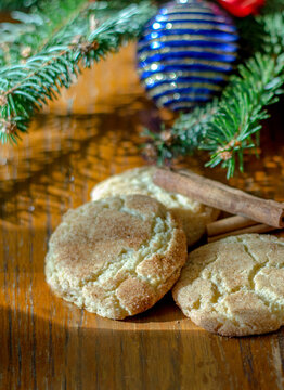 Holiday cinnamon cookies called snickerdoodles,  with Christmas time garnishes of pine , cinnamon and a decorative ornament