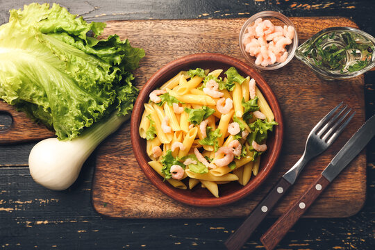 Plate of tasty pasta with shrimps and vegetables on wooden table