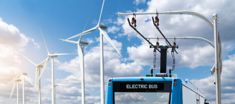 Electric bus at a stop is charged by pantograph on the background of wind turbines