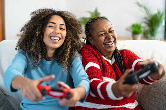 Happy mother and daughter having fun playing video game at home - Gaming entertainment and technology concept