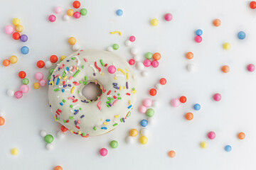 Delicious donut with icing and colorful decoration. Decorated with multicolored candy on white background. Horizontal image. Top view.