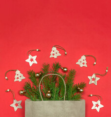 Christmas composition, copy space. Paper bag with Christmas tree branches and wooden toys on red background. Christmas coming and gift delivery concept.
