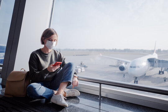 New normal and social distance concept. Young woman tourist wearing mask using smartphone sitting with distance during corona virus 2019 outbreak at airport.