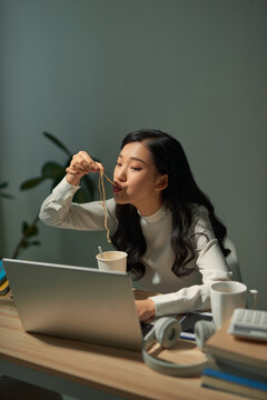 beautiful young lady with overtime doing deadline project and having late night meal