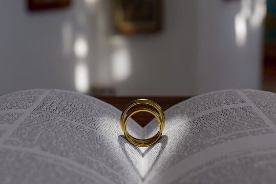 """Two wedding rings on a bible, open to Corinthians Chapter 13, """"The Gift of Love"""" 3D Illustration"""