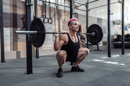 Athletic woman doing squats exercise with barbell on shoulders in modern gym
