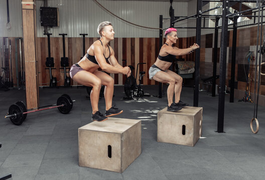 Sporty women doing box jumps together in gym. Training class jumping on wooden boxes in health cross fit club.