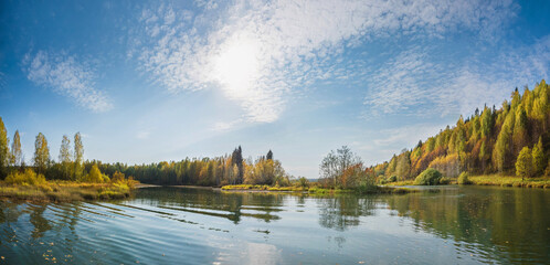 Autumn forest trees are reflected in the river water of the panoramic landscape. Blue sky with clouds.