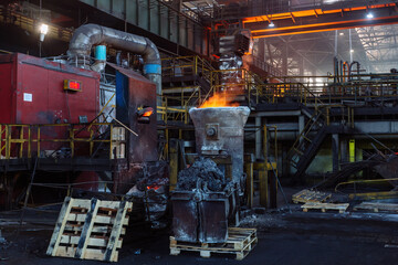 Fototapeta Iron casting and the foundry. Overhead crane with ladle with molten metal at metallurgical factory