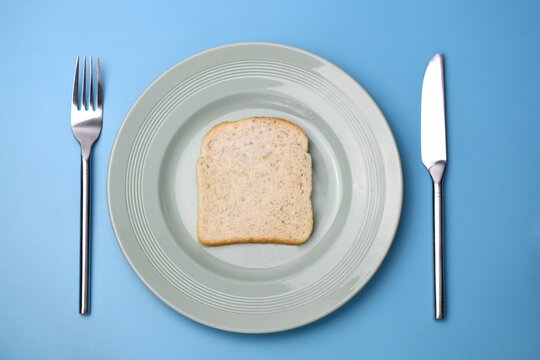 slice of white bread on a plate with fork and knife on blue background
