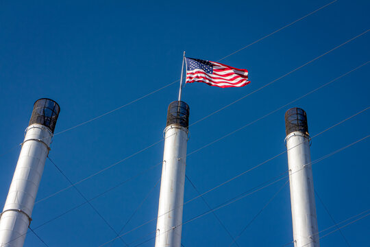 American Flags on top of smoke stacks of a factory