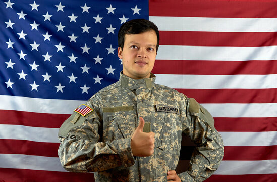 American army soldier on the background of the American flag. Portrait of a US Soldier showing a class gesture. The concept of patriotism
