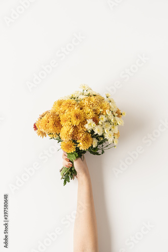 Flatlay of female hand holding yellow and ginger fall wild flowers bouquet isolated on white background. Top view minimalistic floral composition. Valentine's Day, Mother's Day concept.