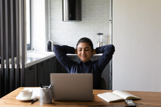Short pause in work. Serene young mixed race woman freelancer working from home office taking break of routine. Indian female relaxing on chair with hands behind head closing eyes breathing fresh air