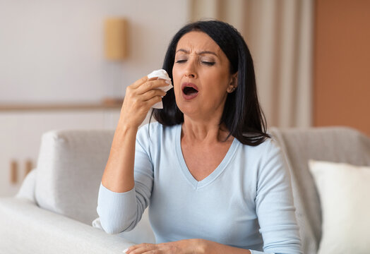 Sick mature woman sneezing and couching, holding tissue paper