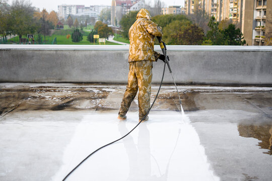 Man in yellow uniform washing roof from dirt. Cityscape visible in the background.