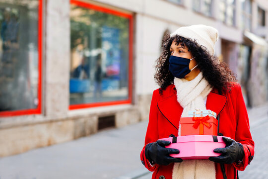 Portrait of a woman in red shopping outside with face mask holding many christmas gifts and presents looking to side