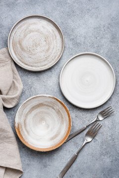 Modern craft ceramic plates made of grey clay. Top view