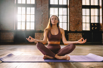 Young woman do complex of stretching yoga asanas in loft style class. Female meditate in lotus position with closed eyes.
