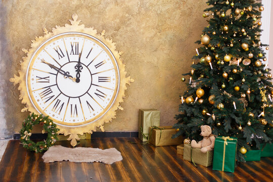 Christmas decoration with vintage clock. Time to New Year, interior with artificial fer-tree, big clock, toys and soft armchair. Brown colors and wooden room.  Comfort home. Christmas presents