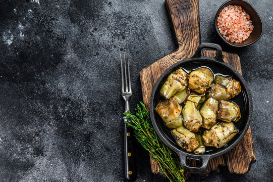 Canned artichokes in olive oil on a rustic wooden kitchen table. Black background. Top view. Copy space