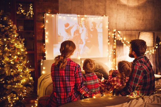 family mother father and children watching projector, film, movies with popcorn in   christmas evening   at home.