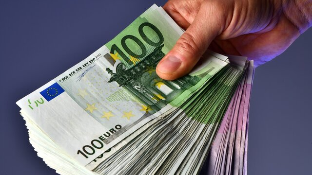 A rich man hand shows 20,000 Euros in 100 euro and 500 euro banknotes on a blue background