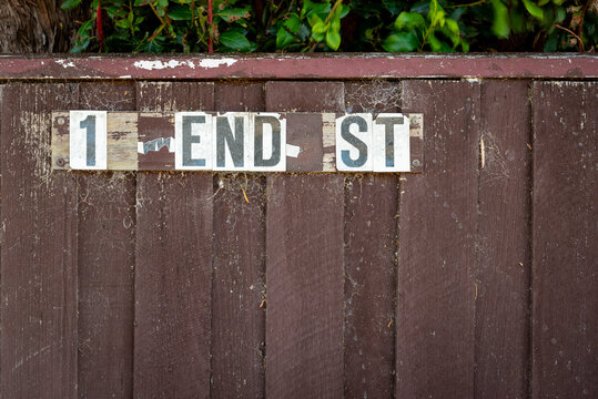 """A broken street address that now reads """"1 End Street"""" which could represent an end of things. Brown dirty fence with leaves and cobwebs, horizontal"""