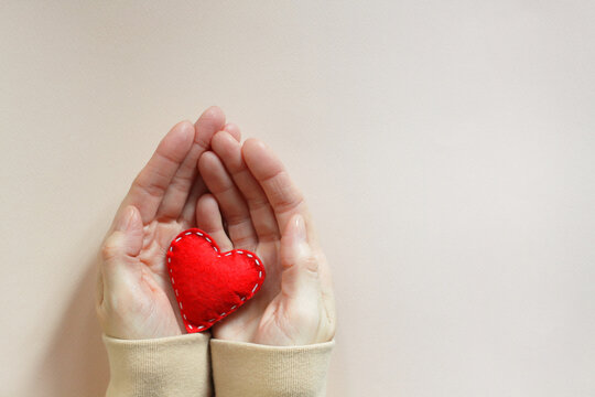 I love you recognition. Female hands and a red felt heart with white stitches on beige paper background.