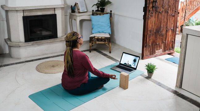 African senior woman doing online yoga lesson at home during coronavirus outbreak - Old female person meditating using computer laptop - Technology and zen concept - Focus on hand