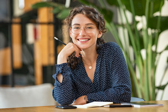 Portrait of happy smiling woman at desk