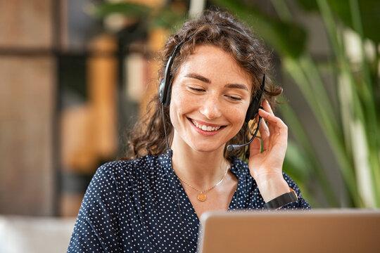 Smiling woman talking to customer on headphones