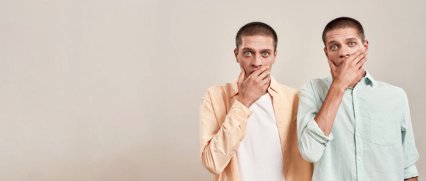 What a surprise. Two young twin brothers covering mouth with hand and looking at camera with shocked face expression while standing isolated over beige background