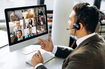 Online video conference. Successful young adult businessman or manager with headphones discuss with...