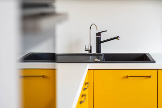 Close-up of black sink and faucet. Modern interior of kitchen. Stylish yellow kitchen set.