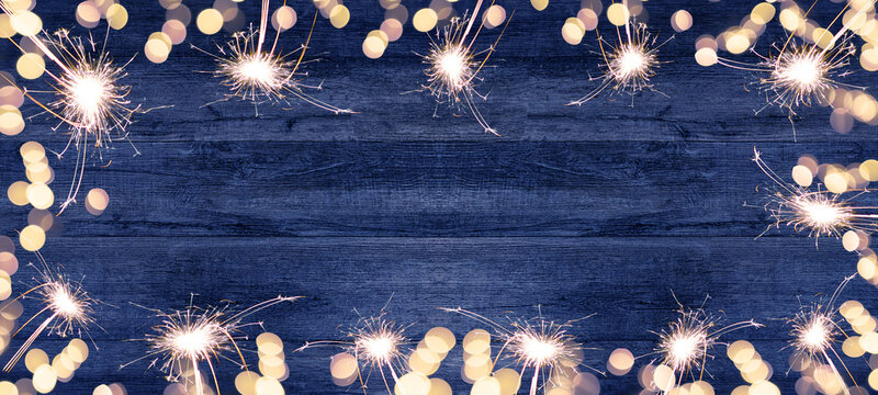 Frame made of lights bokeh flares and sparkler isolated on rustic blue wooden table texture - holiday New Year's Eve background banner, top view with space for text