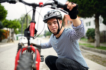 Portrait of down syndrome adult man with bicycle standing outdoors on street.