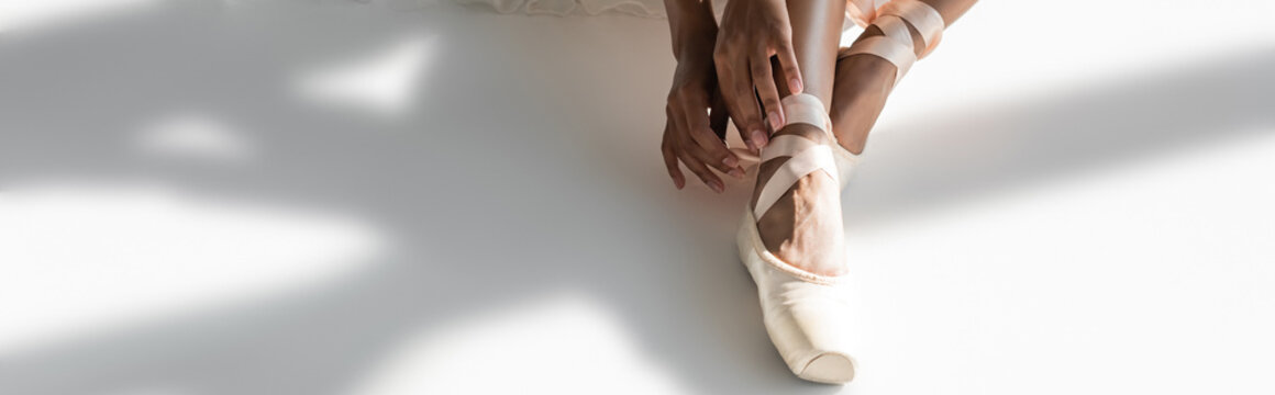 cropped view of graceful african american ballerina in pointe shoes sitting on floor on white background, banner