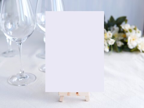 Wedding bar menu template mockup, drinks menu on wooden easel,  white blank card and wine glasses  and flowers in background.