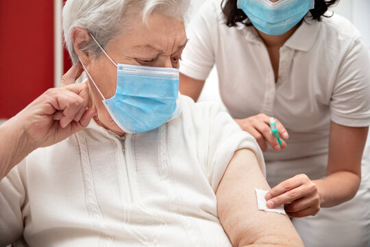 senior adult elderly woman with grey hair is receiving a vaccination against covid